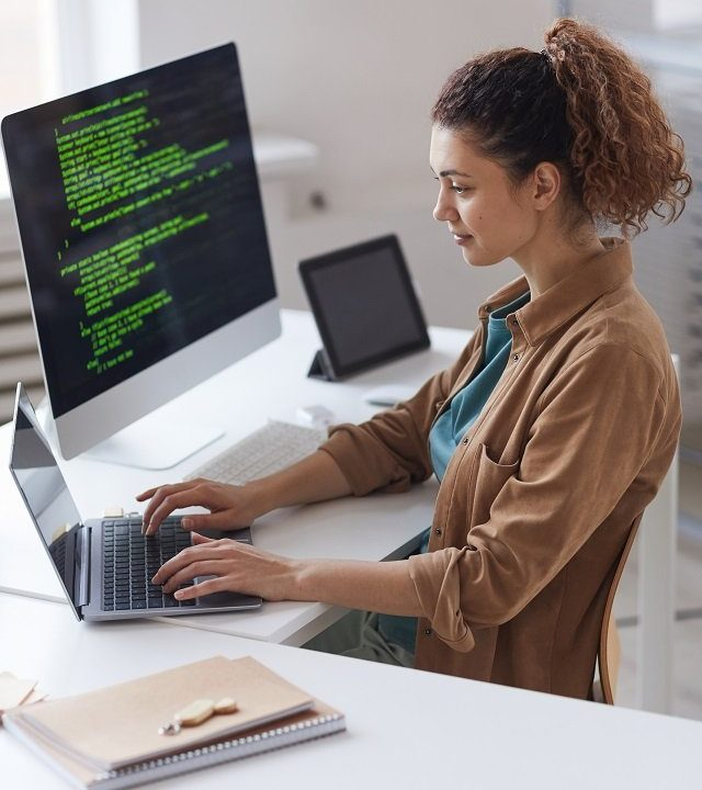 Young woman sitting at the table and concentrating on online work on laptop working at computer service